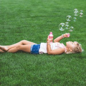 Kid laying in grass blow bubbles